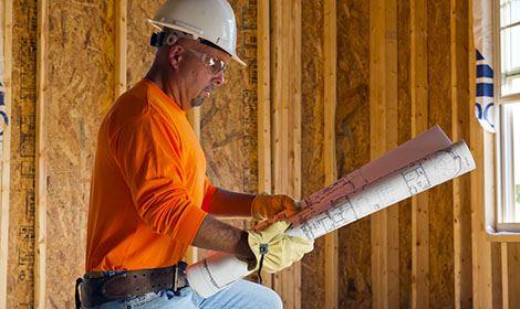 aannemer bekijkt zijn bouwtekening